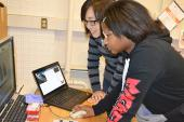 MRL staff member assists middle school student using the scanning electron microscope (Photo by E. Innes, I-STEM)